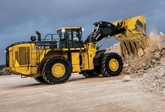 Right hand view of the 944K Hybrid Wheel Loader dumping material out of the bucket