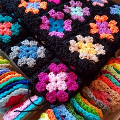 Granny squares blanket in progress, all the tiny squares waiting to be crocheted together in black.