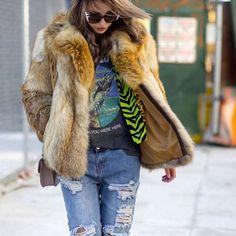 Street style de inverno com calça jeans destroyed, t-shirt e casaco de pele.