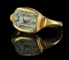 Golden ring with a cameo of green glass showing an eros resting on a torch. Roman, 1st half 3rd century A.D