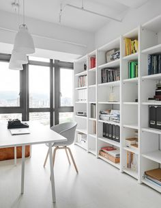 Modern Home Office // A stylish way to organize using an all white storage wall system in this home office in this Minimalist Apartment by Tai & Architectural Design