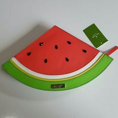 "Kate Spade Slice of Watermelon Clutch Kate Spade Slice of Watermelon red green yellow white and black. SIZE 7.5""h x 12""w x 1.6""d MATERIAL is italian silk satin with matching trim 14-karat light gold plated hardware custom woven two of a kind printed on black  woven jacquard lining DETAILS handheld fruity clutch with zipper closure kate spade new york gold embossed signature. Imported and Constructed from a unique boarskin-embossed cowhide in two contrasting colors, our new concord street…"