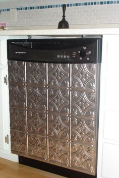 Great Idea! Dishwasher covered in ceiling tiles from Lowes- much cheaper way to match stainless steel fridge.