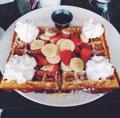 Waffles with strawberries, bananas, powdered sugar, and whipped cream. Easy and delicious.