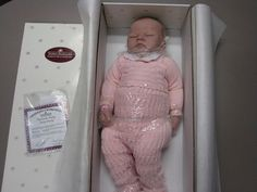 "New Ashton Drake Galleries - ""Welcome Home, Baby Emily"" - New in Box with COA. This vintage porcelain doll comes in a pink knit outfit and has realistic hair and facial features. The doll measures 20"" from the top of the head to its toes and comes in a box that is 22"" x 10 1/2"" x 6"".    This realistic doll is in its original packaging and has never been removed. It includes an unopened Certificate of Authenticity."