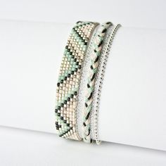 Beaded bracelet made with seed beads and colored cords. Teal, cream, silver and black.