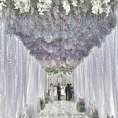 Dreamy decor of @rainforestthewedding with a light grey and violets floral tunnel. Talk about an entrance