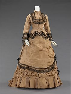 Tan silk walking dress with black lace trim (front), American, 1870-75. This is a nice example of an early 1870s bustle day dress worn for promenading and visiting. Skirt decoration in this period was often achieved by using two separate skirts, with an overskirt being the main source of decoration and the puffing for the bustle.