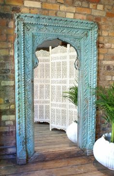Antique turquoise painted antique mirror (sold), leaning against a tan brick wall -- Opium: The Art of Bohemian Living