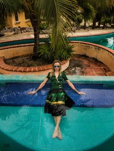Going poolside, Ginta Lapina wears Altuzarra dress and Ray-Ban sunglasses