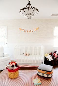 Children's room with red and white striped rug, wood floors, white crib, name banner, light textured walls, white chair, and basket with children's toys