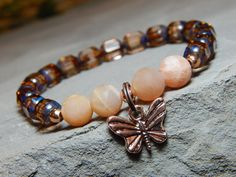 Natural toned Butterfly Bracelet made with a rose gold Butterfly Charm surrounded by 8mm Moonstone and pretty Rose gold czech rondelles. Moonstone Properties: A stone of new beginnings, it is used for