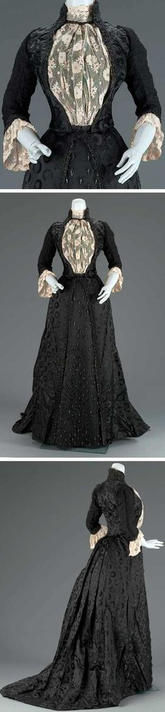 """Woman's dress in two parts (bodice and skirt). Emile Pingat, Paris, ca. 1889. Bodice made of black silk satin damask with circular design, ruched silk chiffon sleeves with lace cuffs, lace collar, appliqued lace center insert, and trimmed with glass beads. Label: """"E. Pingat 30 Rue Louis le Grand 30 Paris"""" Skirt made of black silk satin damask with circular design; center front panel embellished with glass beads. Museum of Fine Arts, Boston"""