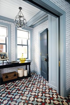 The mudroom can be closed off from the kitchen with a set of pocket doors. James found the light fixture at Reborn Antiques in Los Angeles. A dark-painted door leads to the powder room.