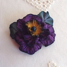 I designed and hand sewed this contemporary ribbon flower with French wired ribbon.  Purple ruffled petals with an antique French rayon pleated ribbon
