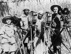 TheJohnsons pose with two unidentified photographers and their manual movie cameras in long grass lands of Africa in 1921