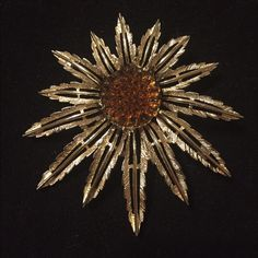 Vintage Sarah Coventry SUNFLOWER SUNBURST BROOCH Exceptional Vintage Signed Sarah Coventry Sunflower Sunburst Pin/Brooch that can convert to a Pendant. This piece looks hardly used and has an abstract, striking design with gold tone sunburst/sunflower leaves and a raised amber center. The pin and clasp are in excellent working condition. There is a hook on the back for a chain or ribbon. Overall dimensions of this piece are approximately 3 inches in diameter from the widest part of the pin…