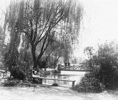 LOS ANGELES-(ca. 1900)^* - View of a woman seated on a bench by Echo Park.  Behind her can be seen two men standing by their bicycles on an ornate bridge.