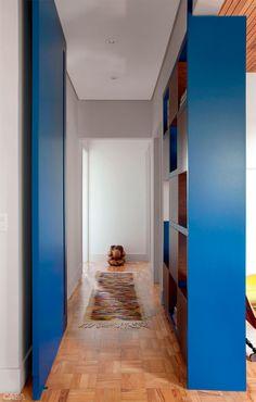 O corredor formado pela porta e o móvel divisória, laqueados de azul