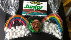 "Girls Scout ""Bridging to Junior"" ceremony treats. A cupcake with green and brown icing. A bag filled with rainbow Twizzlers rainbow and marshmallow clouds.A box of Junior mints embellished with Brownie wing patch, bridge to Junior rainbow award and GS membership star pin."