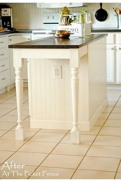 White kitchen with island with turned legs