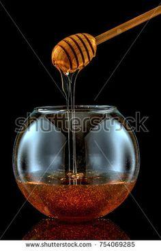 Dripping honey into a decorative jar. On a black background. Buckwheat honey.