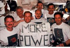 """""""Space Shuttle Discovery - STS-82: The crew poses for a traditional inflight portrait following completion of five space walks to service the Hubble Space Telescope (HST). Both the sign held by the crew and the assortment of apparel pay tribute to the HST and its team of ground supporters. In front, left to right, are astronauts Joseph R. Tanner, Mark C. Lee and Gregory J. Harbaugh. Behind them, left to right, are astronauts Steven A. Hawley, Kenneth D. Bowersox and Scott J. Horowitz...."""""""