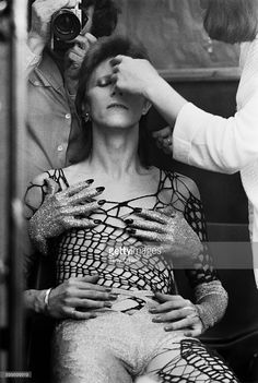 English singer-songwriter David Bowie (1947 - 2016) being made up before filming of 'The 1980 Floor Show', at the Marquee Club, London. He is wearing a cobweb costume with fake hands by Natasha Korniloff. The performance was filmed on 19th and 20th October 1973 for the American NBC TV show 'The Midnight Special'.