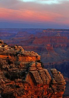 The colors of dawn begin to paint the age-old rock formations along the South Rim near Mather Point.