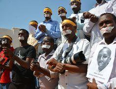 Periodistas somalíes sostienen la imagen de su compañero detenido, Abdiaziz Abdinor Ibrahim, preso por denunciar a la policía. (AFP)