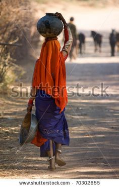 stock photo : Indian woman walking home from the well with water carried in a pot on her head near Udaipur in India January 2007/Carrying water home in India