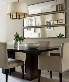 contemporary dining room : use of mirrors : light fixture : table : upholstered chairs : minimalism