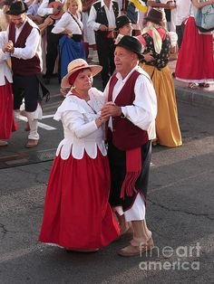 This is a photograph of a mature couple in traditional Canarian costume, dancing in the street during a Romeria.