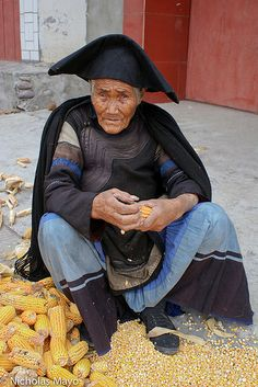 Tu Wu Villager. China A Yi woman, dressed in cape and hat. shucking corn cobs at Tu Wu village.