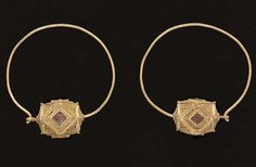 A PAIR OF OSTROGOTHIC GOLD AND GLASS EARRINGS   Circa 6th Century A.D.   Each with a large hoop-shaped earwire, round in section, threaded through a hollow polygonal bead and formed into a hook-and-loop closure, the bead perforation rimmed with beaded wire, four faces of each bead set with garnet-colored glass, the entire surface of the bead patterned with fine granulation  2 7/8 in. (7.3 cm) wide