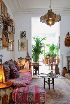 Moroccan interior design inspiration. Loving everything about this photo! The colors, couch, the plants, the tribal masks and the butterfly wall frame...