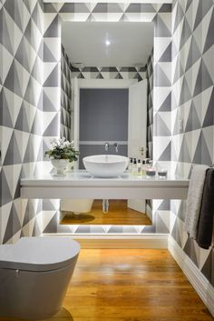 Small, simple, modern bathroom with wooden floors and geometric wallpaper design. mirrorCasa de banho social : by LAVRADIO DESIGN