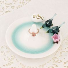 A pretty blush pink flower is the perfect compliment to an Aqua love bird pair on this beautiful wedding ring holder.
