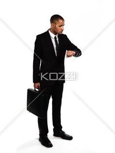 impatient businessman checking the time. - Impatient businessman checking the time against white background, Model: Kareem Duhaney