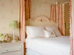 Curtains with coral and beige stripes add drama to this canopy bed and unify the muted colors in this little girl's room. Colorful tassels line the edge of the curtains for a fun and playful touch. All-white bedding complements the white nightstand while an ornate pink and cream headboard uses the same colors in the patterned wallpaper.