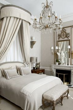 Another superbly designed bedroom! The high ceiling, emphasized by the bed crown & draperies, is balanced by the lovely mirror & fireplace. Restful & elegant.