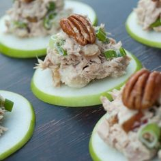 Apples sliced thin with chicken salad and a whole pecan on top.