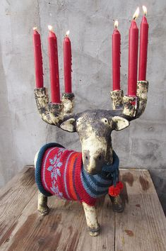 This stag is made of fireclay, it has been colored with metal oxides and fired at 1050 °C in an electric kiln. There are felt stickers on its soles.  It wears a hand knitted striped wool sweater with bow detail and two pom poms in front.  Because the wax could drip when the flames