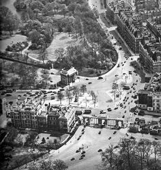 An aerial view of Hyde Park Corner before the changes made in the early 1960s. Great swathes of Green Park and the gardens of Buckingham Palace were taken for the roundabout leaving the Constitution Arch marooned in a sea of traffic.