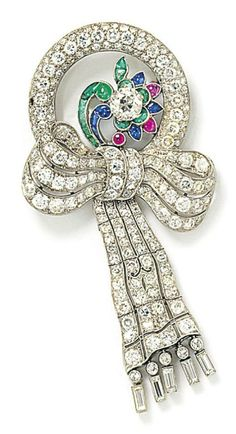 An Art Deco gem-set brooch. The old brilliant-cut diamond within a cabochon emerald, ruby and sapphire flowerhead cluster, set within a pavé old brilliant-cut diamond circlet, to an old brilliant-cut diamond pierced bow and articulated ribbon, with baguette-cut diamond fringe base. #ArtDeco #brooch