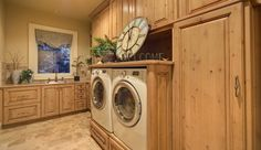 WOW!  I think this is the nicest laundry room I've seen.  Love the stationary large window that lets in natural light and the alder cabinets.  Notice the custom platforms for the washer/dryer.
