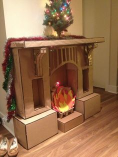 """Homemade """"fireplace"""" out of cardboard boxes and package paper. Just the photo, but great inspiration."""
