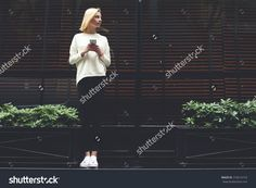 Full length portrait of gorgeous young woman holding smart phone in hand and looking to the empty copy space area for your text message or information,female hipster have chat conversation on phone