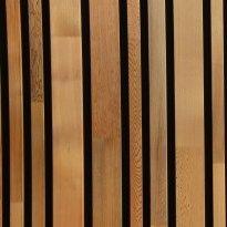 Massief houten gevelbekleding met afstand ertussen en erachter zwart regendicht doek.