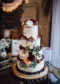 Burgundy and white naked wedding cake. greenery